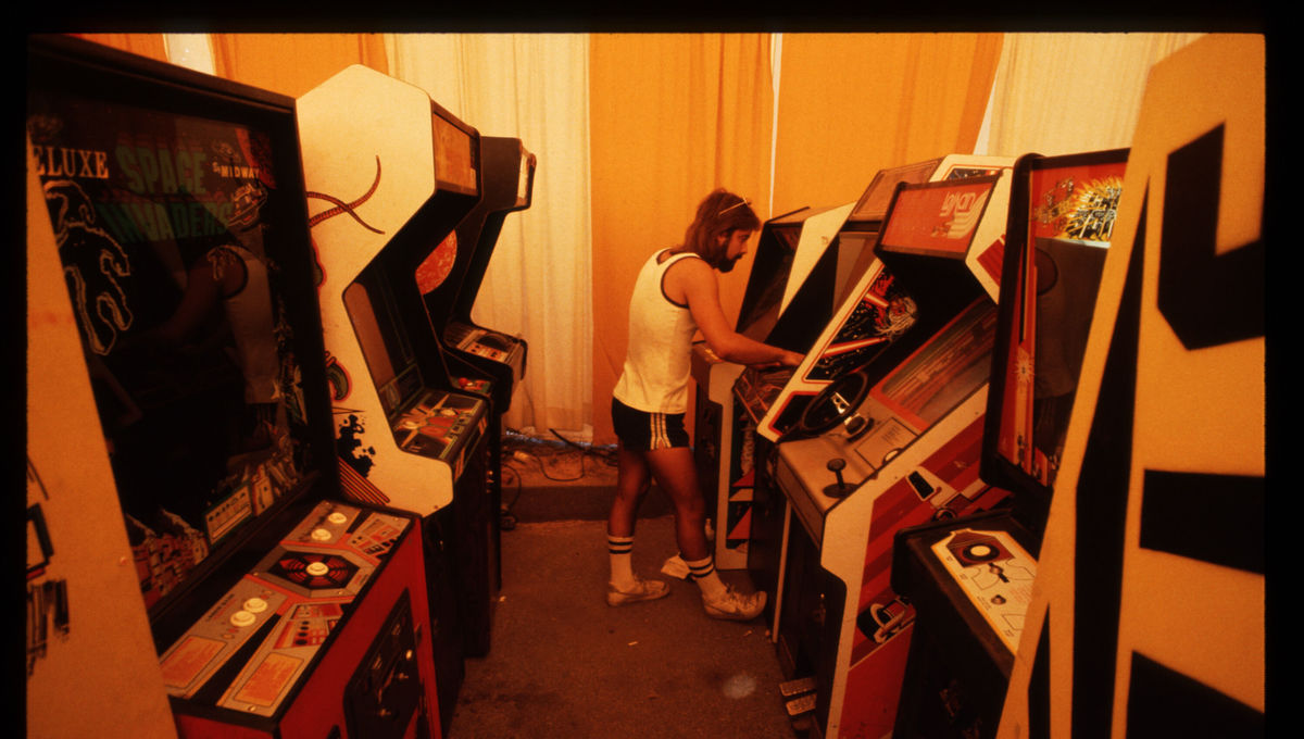 Man playing video game at 1980s arcade