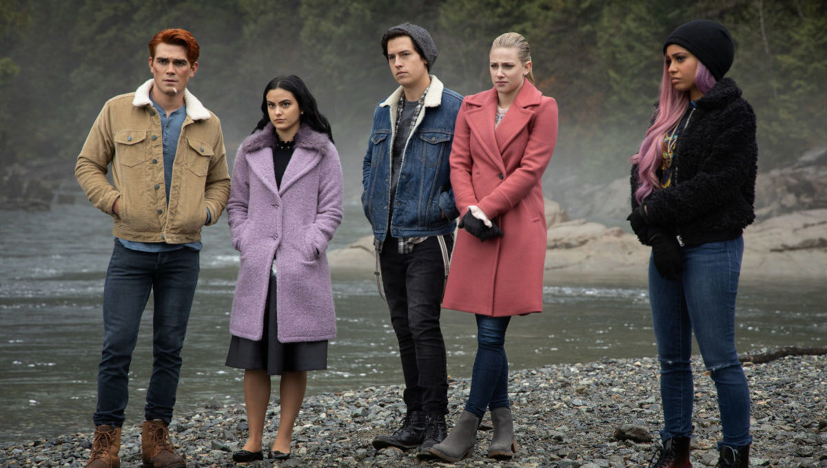 The teens of Riverdale stand by a river.