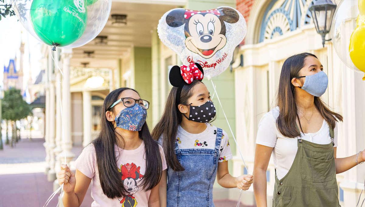 Three guests holding Disney balloons walking down Main Street, USA at Disney's Magic Kingdom