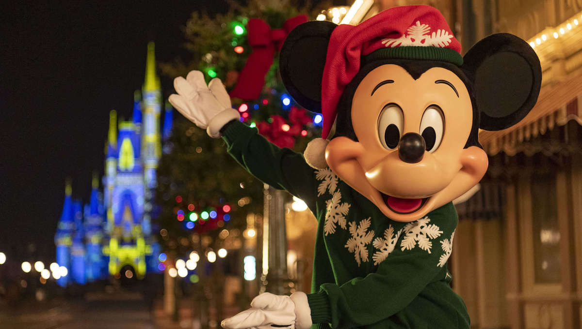 Mickey Mouse dressed for winter and pointing at the castle