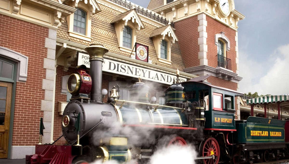 Disneyland steam train in front of a Disneyland sign