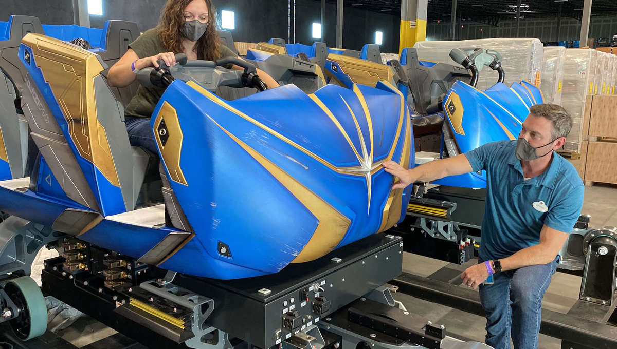 Two people working on the colorful roller coaster ride vehicle that will be used for the Guardians of the Galaxy: Cosmic Rewind ride