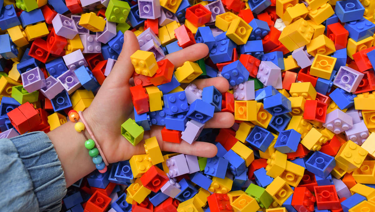 LEGO pile with hand Getty