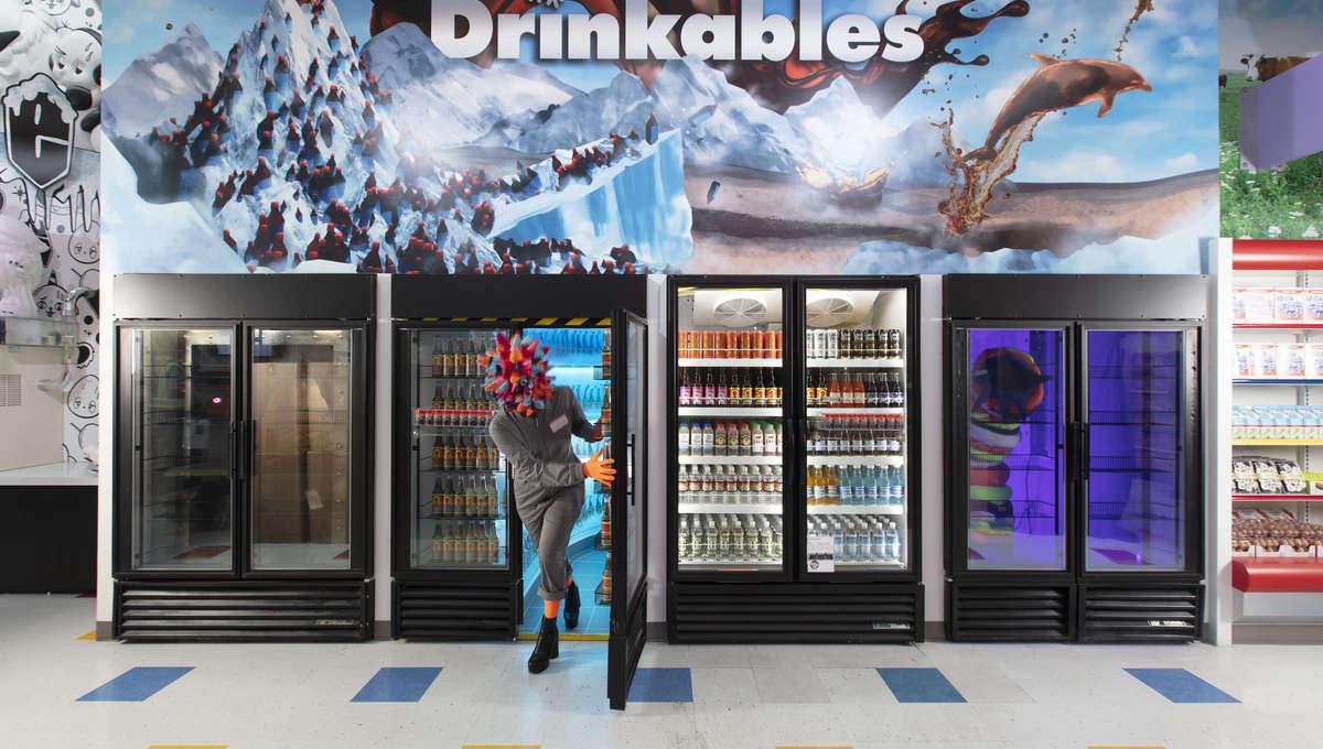An Omega Mart employee entering a grocery store through a facade of a fridge