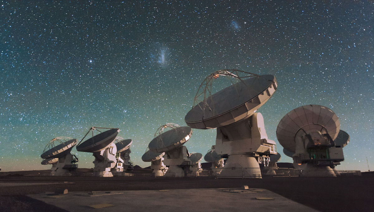 Some of the dishes comprising ALMA, the Atacama Large Millimeter/submillimeter Array in the high desert plain of Chile. The Large and Small Magellanic Clouds, companion galaxies to the Milky Way, can be seen above them. Credit: ESO/ C. Malin