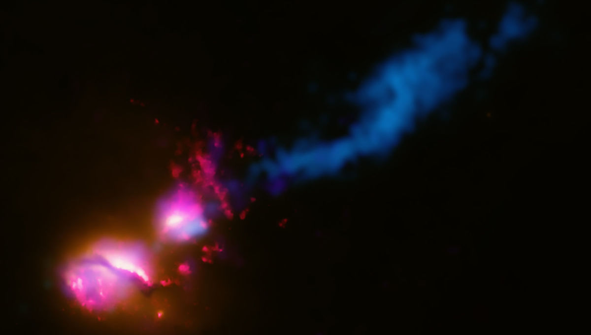 Data from across the electromagnetic spectrum are combined to show that the galaxy 3C321 (lower left) is blasting out a jet of matter that is slamming into a neighboring galaxy (middle) which deflects the jet somewhat (blue, upper right). Credit: X-ra