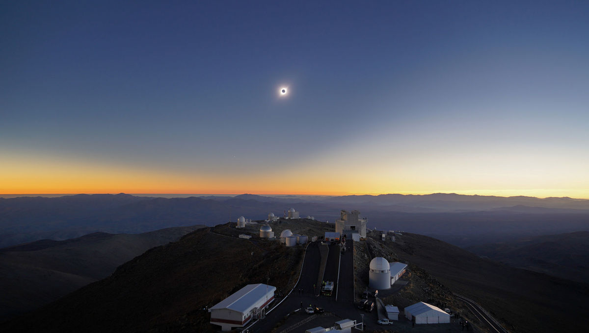 "The total solar eclipse of July 2, 2019 over the ESO's La Silla astronomical observatory in Chile. You can see the shadow of the Moon on the sky itself, a lopsided curve due to perspective. The ""star"" to the lower left is actually the planet Venus."