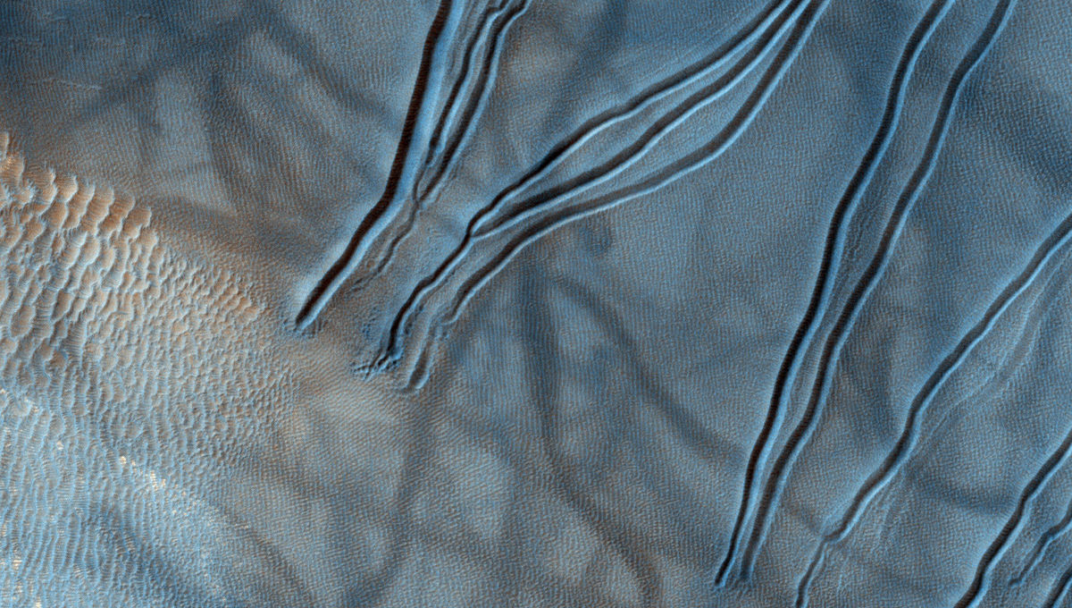 A color close-up image of gullies on Mars shows dimpling near their source, implying subsurface materials sublimating in the warmer seasonal weather. Credit: NASA/JPL/University of Arizona