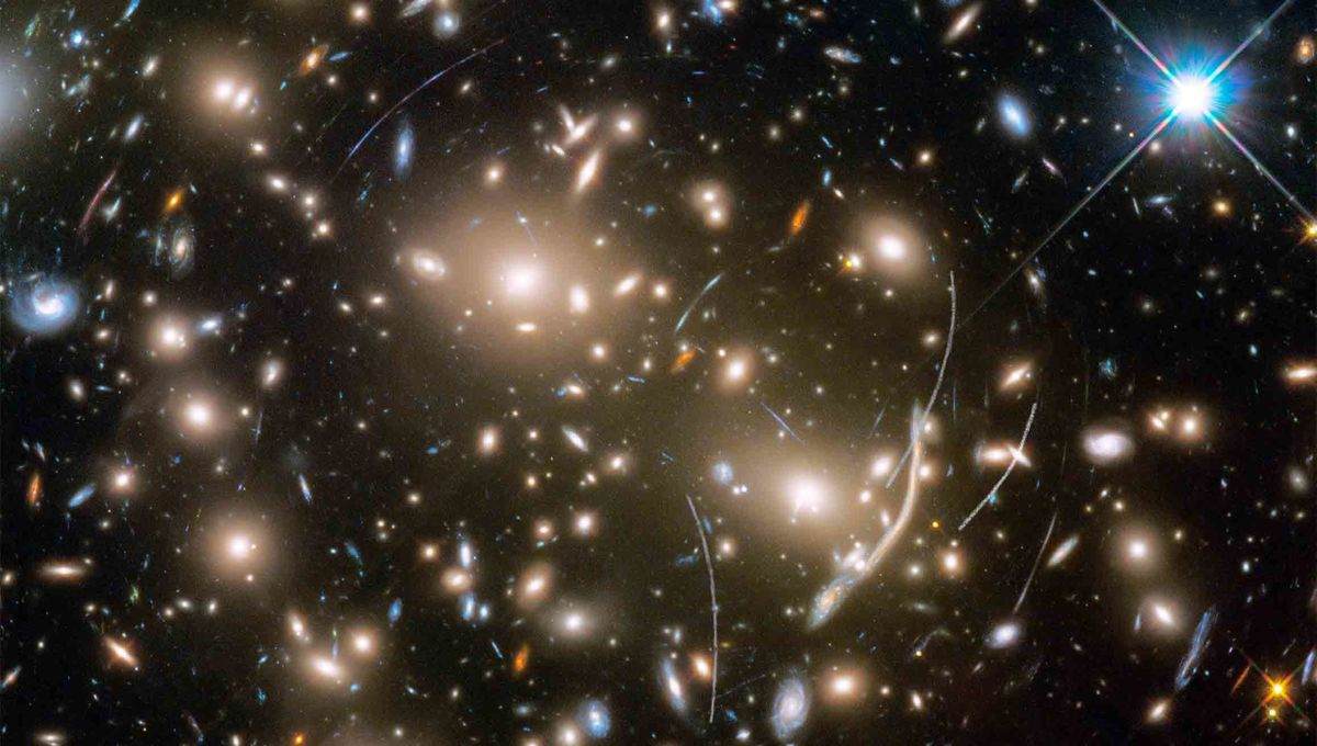 Abell 370 provides a dramatic backdrop for quite a few asteroids, seen as curved tracks in this Hubble image. Credit: NASA, ESA, and B. Sunnquist and J. Mack (STScI) Acknowledgment: NASA, ESA, and J. Lotz (STScI) and the HFF Team