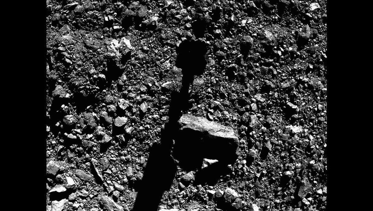 Moments before sample collection, the OSIRIS-REx boom and sample collector shadow stretched across the surface of the asteroid Bennu. Most of those rocks are a few centimeters across. Credit: NASA/Goddard/University of Arizona/Lockheed Martin