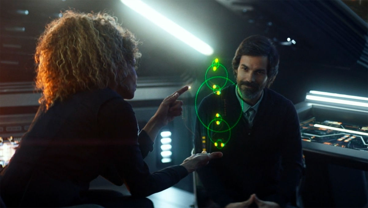 "Raffi shows Enoch, the navigational hologram, a schematic of an octonary, an eight-star system, as shown in the Star Trek: Picard episode, ""Broken Pieces"". Credit: CBS"