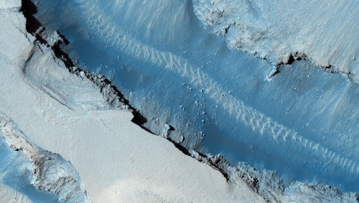 Sand dunes ripple across the floor of a graben in Cerberus Fossae on Mars in this enhanced color image (Mars is dark grey and ochre, not blue). Credit: NASA/JPL-Caltech/University of Arizona