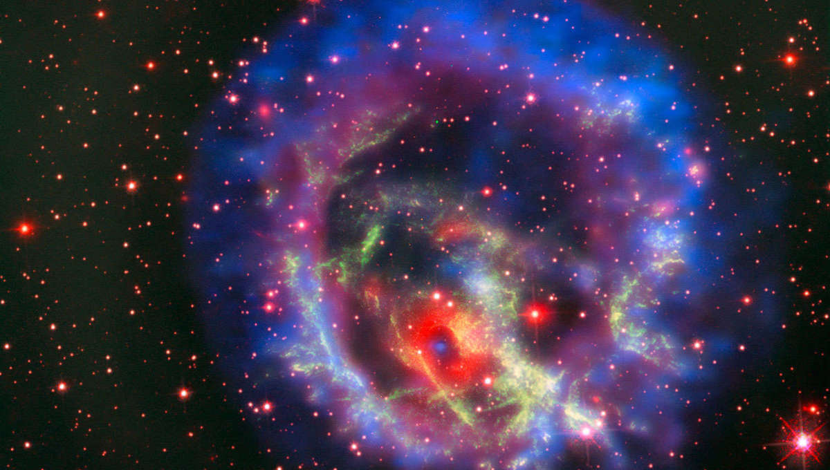 The supernova remnant 1E 0102.2-7219 seen by three telescopes: The red background (note the stars) from Hubble, the Very Large Telescope in green, and X-rays seen by Chandra X-ray Observatory in blue and purple.