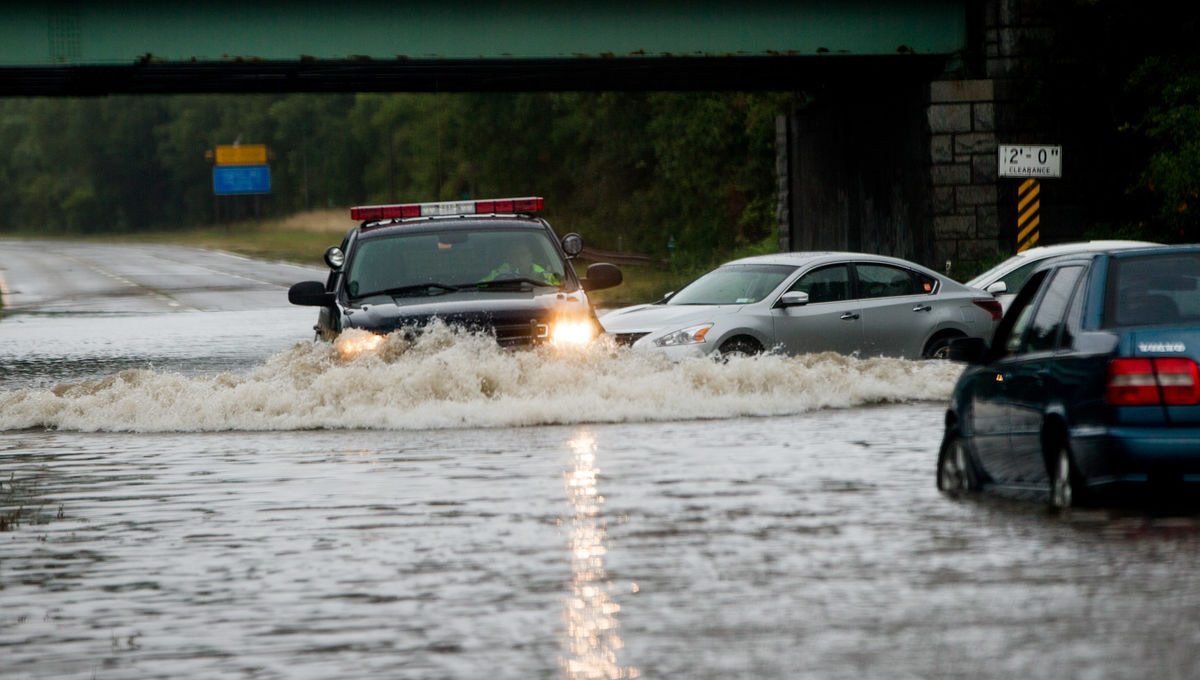 453561078-police-officer-drives-past-flooded-cars-abandoned-on.jpg