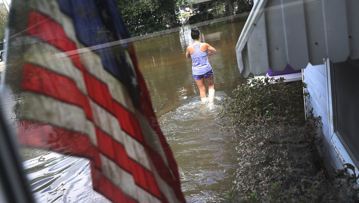 591968858-wanda-sittig-walks-through-the-flood-waters-around-her_0.jpg