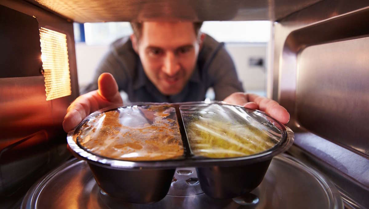 bigstock-Man-microwave-Dinner-Into-Mic-77372021.jpg