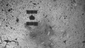 As Hayabusa2 ascends after (hopefully) retrieving a sample from the asteroid Ryugu, its shadow can be seen over the blast mark left from the projectile that dislodged surface rocks. Credit: JAXA