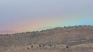 The very tippy top of a rainbowpeeks out above the Colorado Rocky Mountain foothills. Credit: Phil Plait