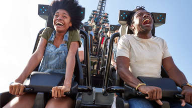 Two passengers screaming while aboard the Jurassic World VelociCoaster roller coaster