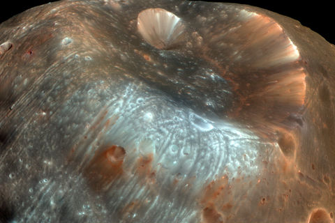 A color-enhanced image of the crater Stickney and some of the grooves covering Phobos, a moon of Mars. Credit: NASA/JPL-Caltech/University of Arizona
