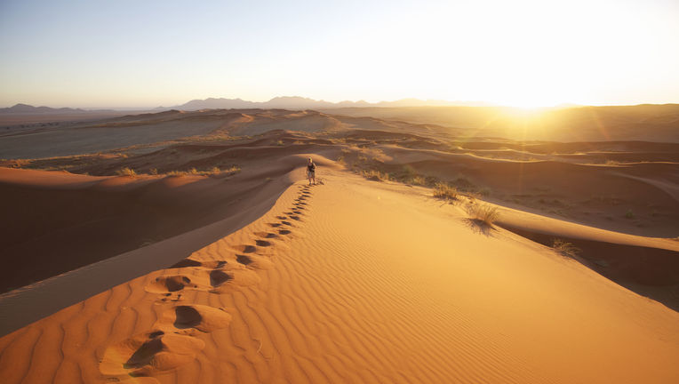 A person walking up a sand dune, Keetmashoop, Namibia Namibia, officially the Republic of Namibia, is a country in Southern Africa whose western border is the Atlantic Ocean. It shares borders with Angola and Zambia to the north, Botswana and Zimbabwe to
