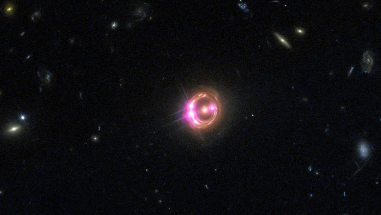 The quasar RX J1131-1231 appears as a series of bright dots on a ring around the fuzzy elliptical galaxy in the center due to gravitational lensing. This is a Hubble image (red, green, and blue) combined with Chandra which sees X-rays (displayed as pink).