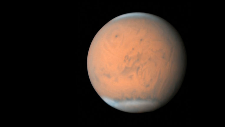Mars on June 28, 2018, shows the extent of the storm. The peak of Olympus Mons (at 25 km high!) shows over it, as well as other volcanoes, while other features are hard to distinguish (a map on the right provides context). Credit: Damian Peach
