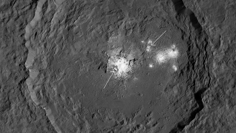 Occator crater, a 92-kilometer-wide impact feature on Ceres, is covered in mineral deposits dredged up from the interior. Cerealia Facula is arrowed (left) as well as Vinalia Faculae (right). Credit: NASA/JPL-Caltech/UCLA/MPS/DLR/IDA/PSI / Phil Plait