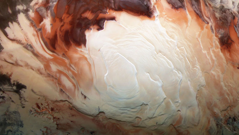 The southern polar ice cap of Mars (using infrared, green, and blue light), which is mostly water ice with a thin layer of carbon dioxide ice on top, taken by Mars Express. Credit: ESA / G. Neukum (Freie Universitaet, Berlin) / Bill Dunford