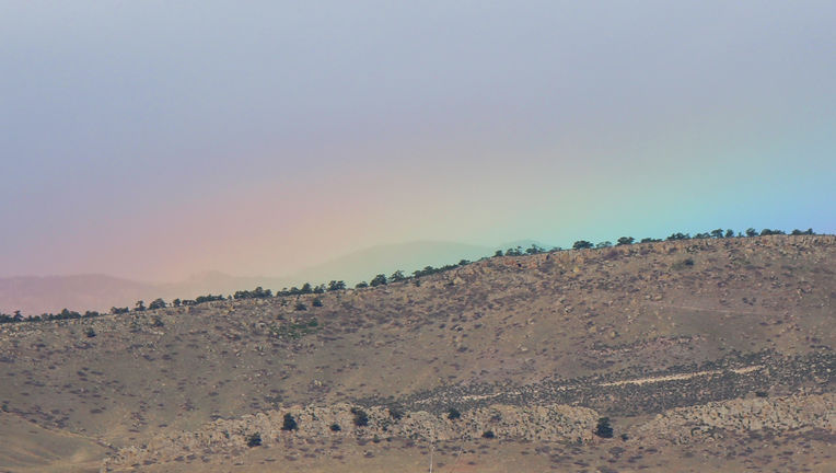 The very tippy top of a rainbow peeks out above the Colorado Rocky Mountain foothills. Credit: Phil Plait