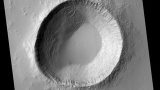 A spectacular if oddly shaped crater near the equator on Mars, situated between two ancient volcanoes. Credit: NASA/JPL/University of Arizona